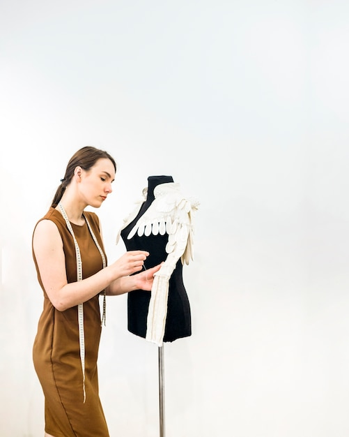 Young female designer sewing dress in shop Free Photo