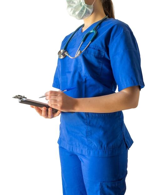 Молодая женщина-врач в синей медицинской форме и маске делает заметки в записной книжке Бесплатные Фотографии