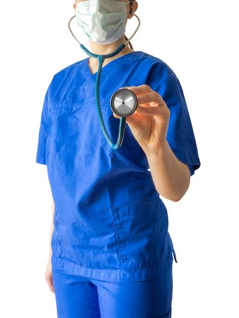 白い背景に分離された聴診器を保持している青い医療服の若い女性医師 無料写真