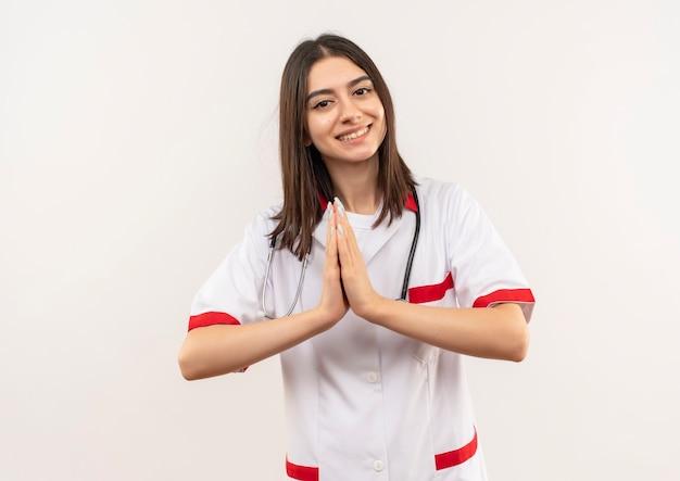 首に聴診器を持った白いコートを着た若い女性医師が、白い壁の上に立って感謝しているナマステジェスチャーのように手をつないでいます 無料写真