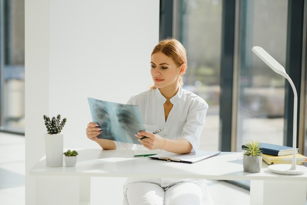 Молодая женщина-врач смотрит на рентгеновский снимок легких в больнице Premium Фотографии