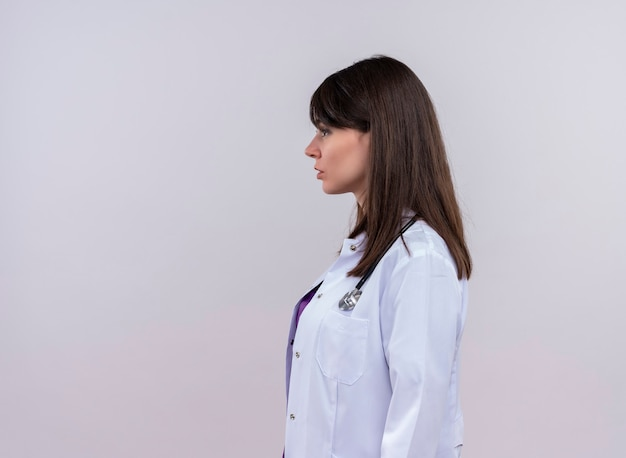 La giovane dottoressa in abito medico con lo stetoscopio si leva in piedi lateralmente sulla parete bianca isolata Foto Gratuite