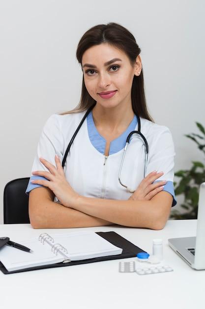 Giovane medico femmina seduto con le mani incrociate Foto Gratuite