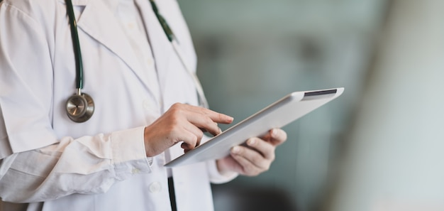 Young female doctor summarises patient charts with digital tablet Premium Photo
