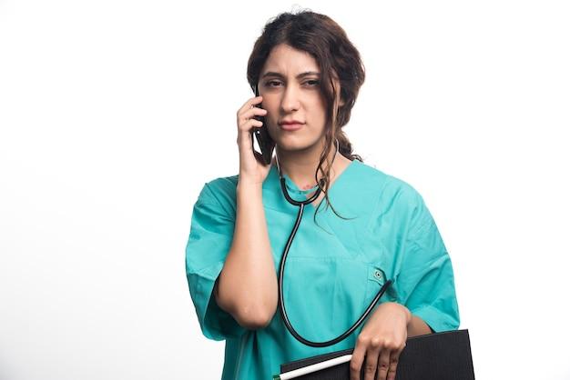 Молодая женщина-врач с буфером обмена и держа сотовый телефон на белой предпосылке. фото высокого качества Бесплатные Фотографии