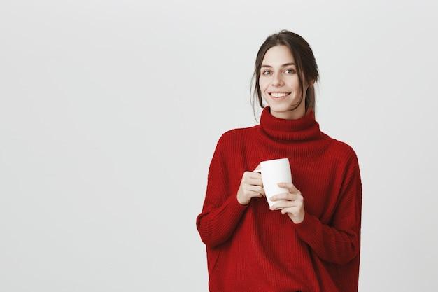 コーヒーを飲みながら、マグカップを押しながら笑顔の若い女性従業員 無料写真