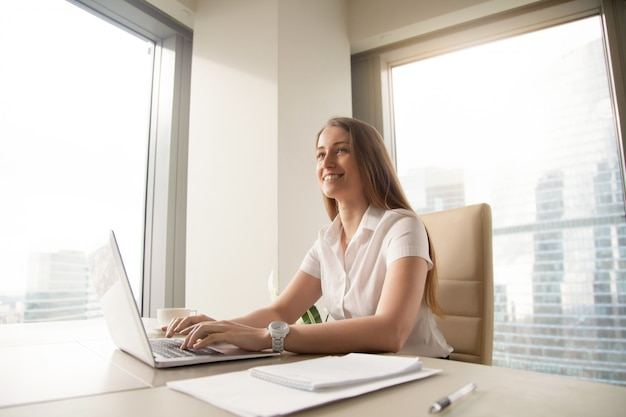 Young female entrepreneur feels happy at workplace Free Photo