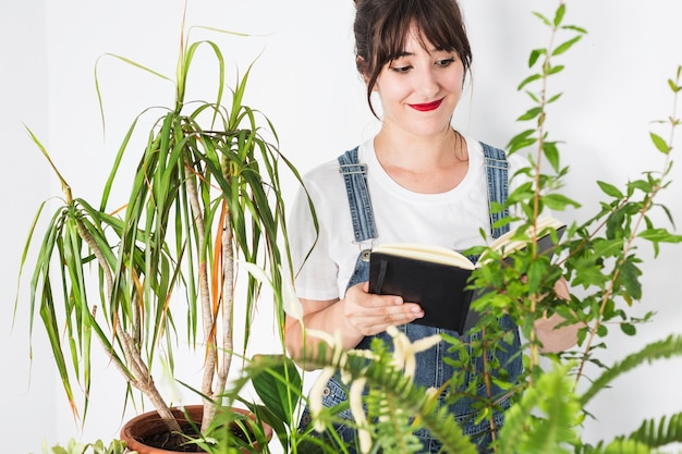 Young female florist with diary looking at plants Free Photo