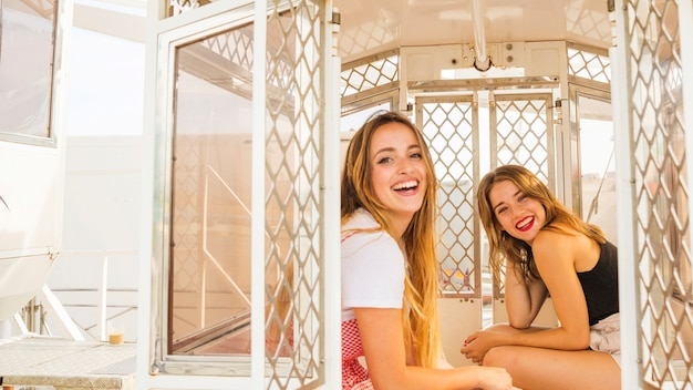Young female friends enjoying in the ferris wheel cabin Free Photo