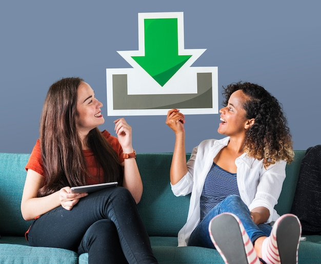 Young female friends holding a download icon Free Photo