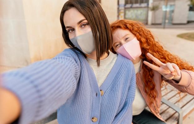 Giovani amici di sesso femminile con maschere facciali all'aperto prendendo un selfie Foto Gratuite