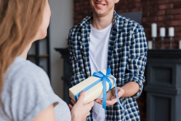 Young female giving gift to husband Free Photo