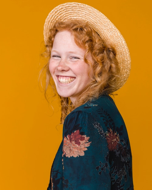 Young female in hat and with curly hair smiling Free Photo