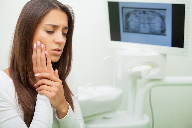 Young female having toothache. upset woman at the dentist. constant pulsating pain Premium Photo