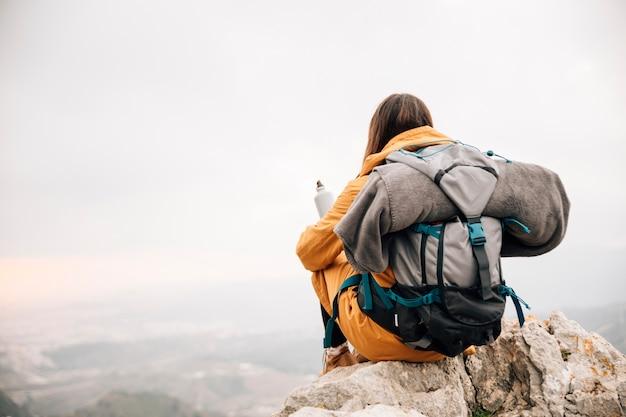 山を見下ろす水のボトルを保持している彼女のバックパックで若い女性ハイカー Premium写真