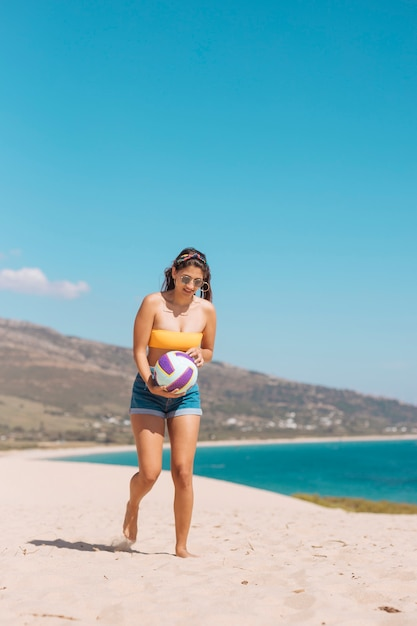 Young female holding ball by seashore Free Photo