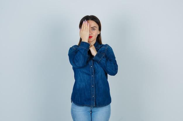 Giovane donna che tiene la mano sull'occhio in jeans e camicia di jeans e che sembra serio Foto Gratuite