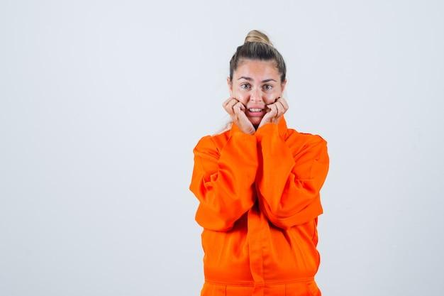 Giovane donna che si tiene per mano sulla mascella caduta in uniforme da lavoro e guardando ansioso, vista frontale. Foto Gratuite