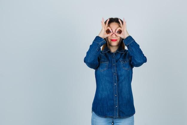 デニムシャツとジーンズの若い女性がメガネのジェスチャーを示し、かわいく見える 無料写真