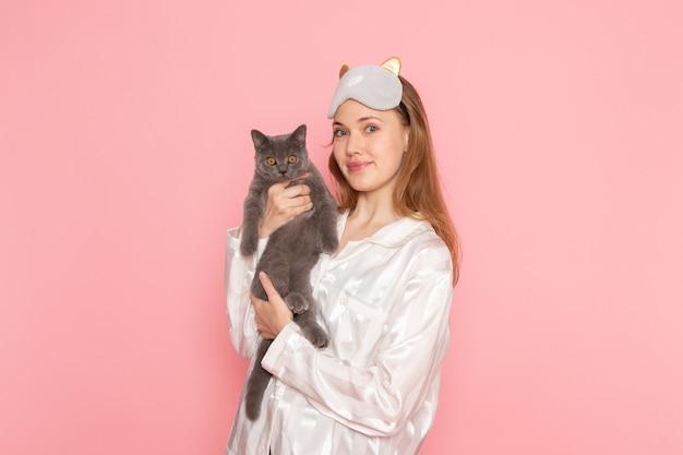 パジャマとピンクのかわいい灰色の猫を保持している睡眠マスクの若い女性 無料写真