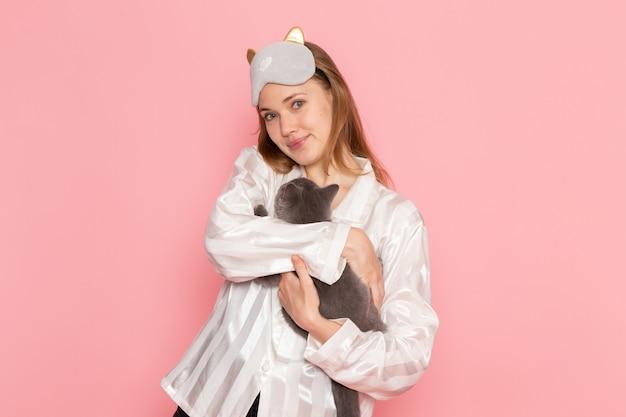 パジャマとピンクの灰色の子猫を保持している睡眠マスクの若い女性 無料写真