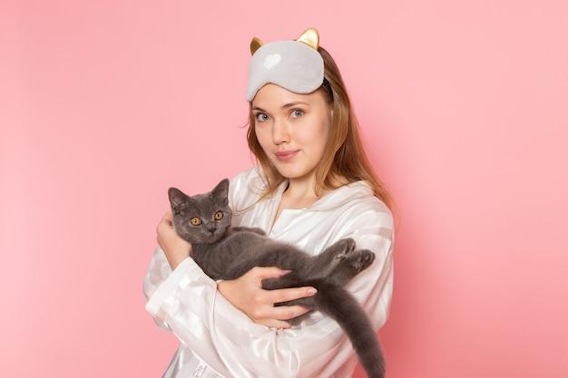 パジャマと少し笑顔とピンクの猫とポーズ睡眠マスクの若い女性 無料写真