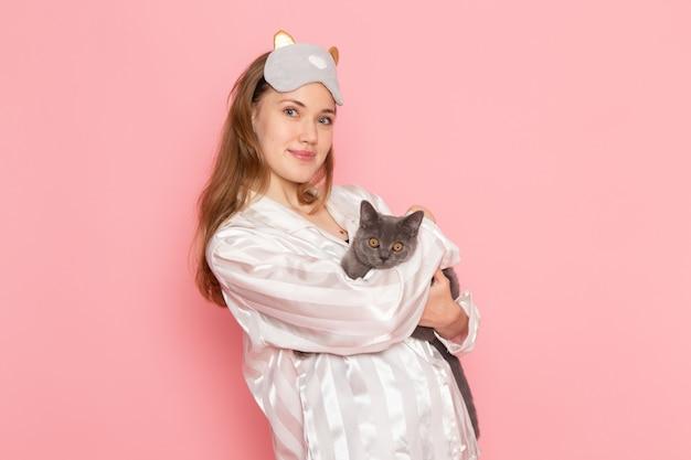 パジャマとピンクの笑顔と灰色の子猫でポーズ睡眠マスクの若い女性 無料写真