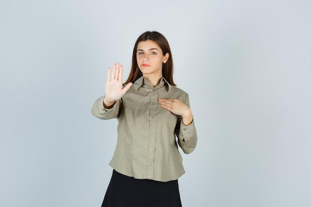 Молодая женщина в рубашке, юбке показывает жест отказа, держа руку на груди Бесплатные Фотографии