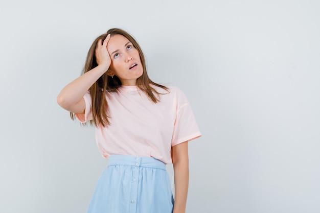 Молодая женщина в футболке, юбка смотрит вверх и задумчиво, вид спереди. Бесплатные Фотографии