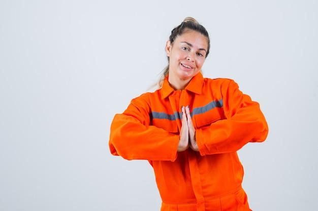 ナマステのジェスチャーを示し、嬉しそうに見える労働者の制服を着た若い女性、正面図。 無料写真