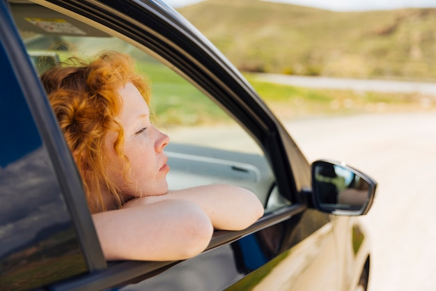 Young female looking out of car window Free Photo