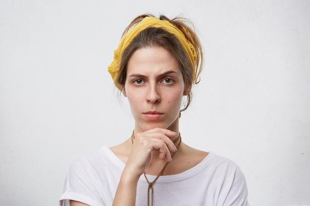 Giovane femmina che sembra scettica e che tiene la mano sul mento. Foto Gratuite