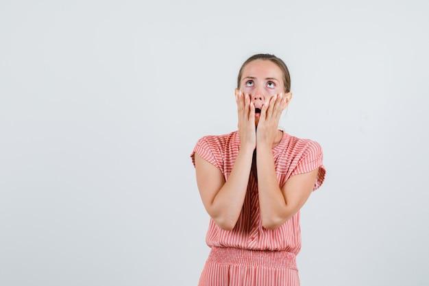 Молодая женщина смотрит вверх руками на щеках в полосатом платье и выглядит испуганной, вид спереди. Бесплатные Фотографии