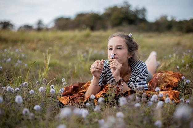 Молодая женщина, лежа в поле цветов в дневное время Бесплатные Фотографии