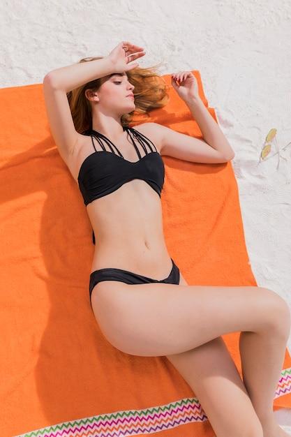 Молодая самка лежит на оранжевом полотенце Бесплатные Фотографии