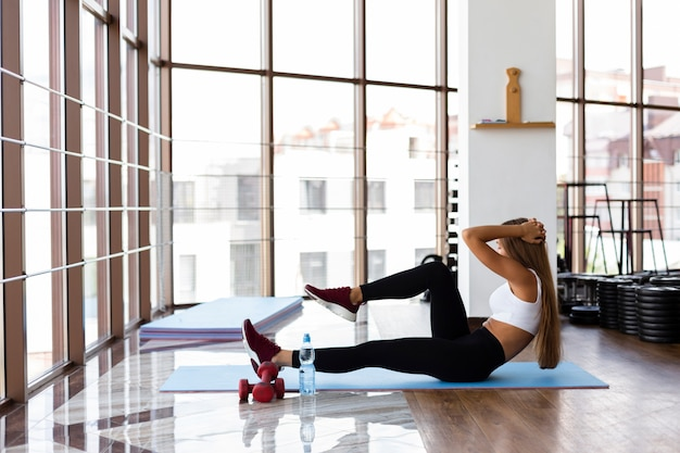 Young female on mat exercising Free Photo
