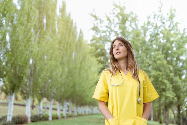 物思いにふける空気を持つ若い女性看護師 Premium写真