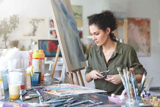 Молодой женский художник сидя на таблице окруженной различными кистями и акварелями пока создающ красивое изображение на мольберте. творческий работник работает на холсте. ремесло и художественная концепция Бесплатные Фотографии