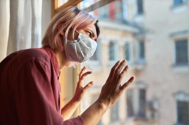 La giovane paziente con sintomi di covid-19 deve rimanere in ospedale durante la quarantena, in piedi vicino alla finestra nella mascherina chirurgica usa e getta, avendo sottolineato lo sguardo paranoico, tenendo le mani sul vetro Foto Gratuite