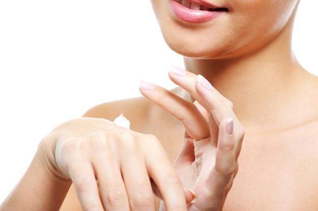 화장품 크림을 적용하는 그녀의 손을 돌보는 젊은 여성 사람 무료 사진