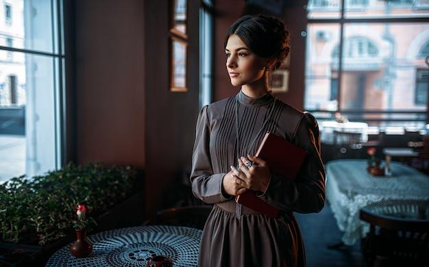 本と窓の近くに立っている若い女性の人 Premium写真