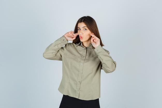 Giovane femmina tappando le orecchie con le dita, mantenendo le labbra piegate in camicia Foto Gratuite