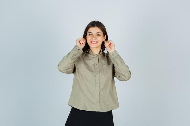Молодая женщина опускает мочки ушей в рубашке, юбке и выглядит весело Бесплатные Фотографии