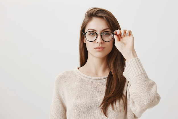 Young female put on glasses, looking determined Free Photo