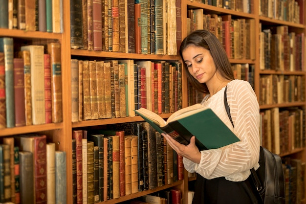 Young female reading book and leaning on shelf Free Photo