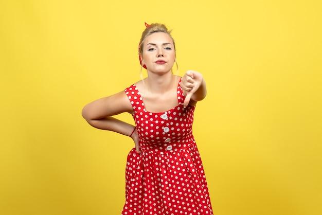 Giovane donna in abito rosso a pois mostrando segno diverso sul giallo Foto Gratuite