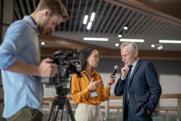 Молодая женщина-репортер берет интервью у известного бизнесмена Premium Фотографии