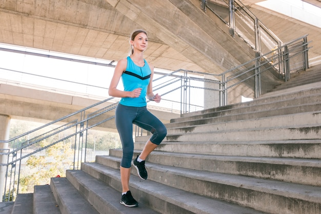 Young female runner jogging on concrete staircase Free Photo