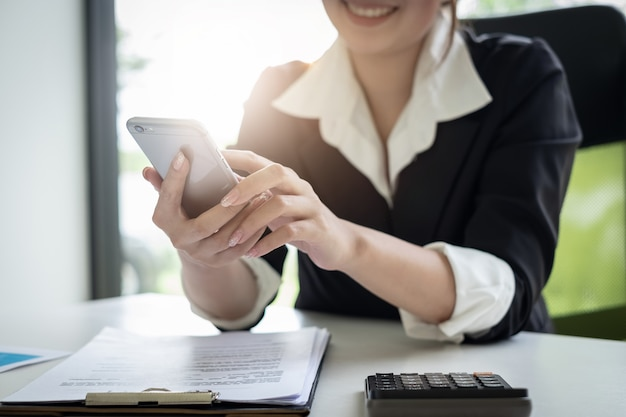 Young female secretary holding phone for contact customer meeting schedule Premium Photo