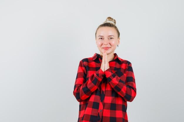 チェックシャツでナマステのジェスチャーを示し、陽気に見える若い女性、正面図。 無料写真